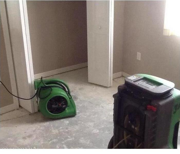 Bedroom with pulled out flooring and closet; green vacuum and water removal equipment.