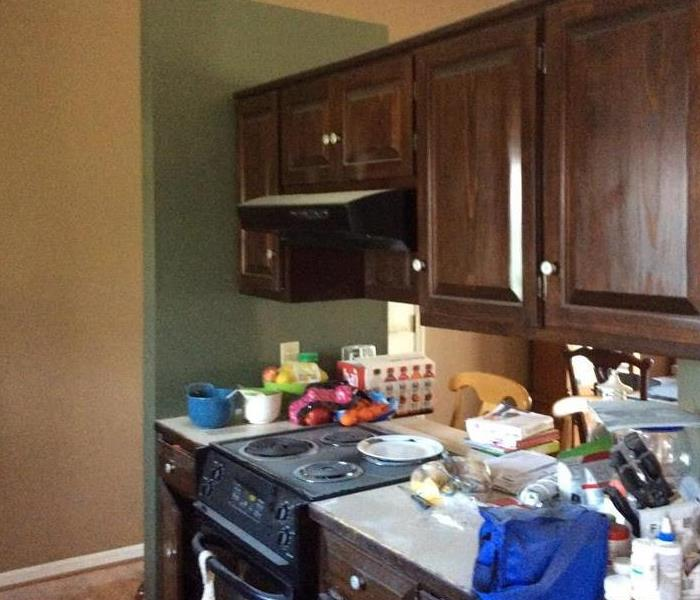 cherry cabinet kitchen with black stove and various food items on counter.