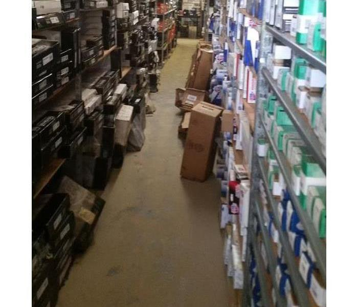 aisle of store with shelving the top with various auto tools. The tiles flooring contains boxes and dagme from the storm.