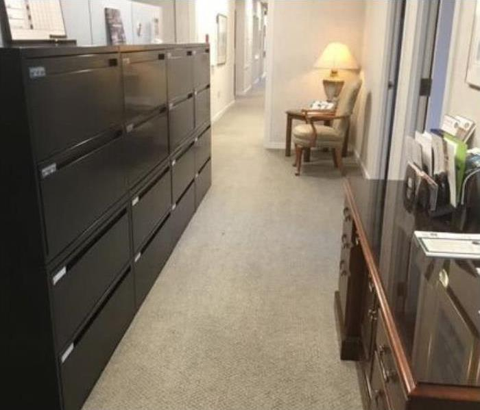 dirty beige carpet with black filing cabinet with multiple drawers to the left and brown desk to the right and chair