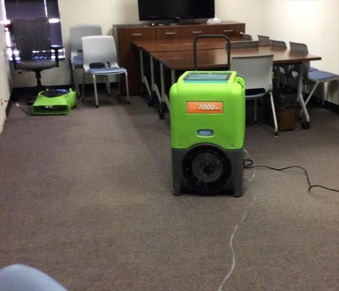 conference room with wheeled chairs and tables pushed towards the back; green vacuum on the floor and other SERVPRO equipment