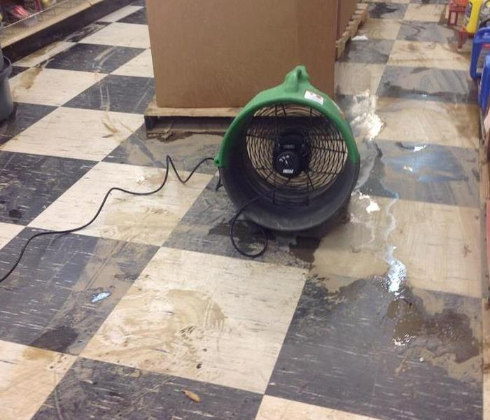 water damaged floor with off-white and blue squares. Green fan and shelving with tools on them in the corner.