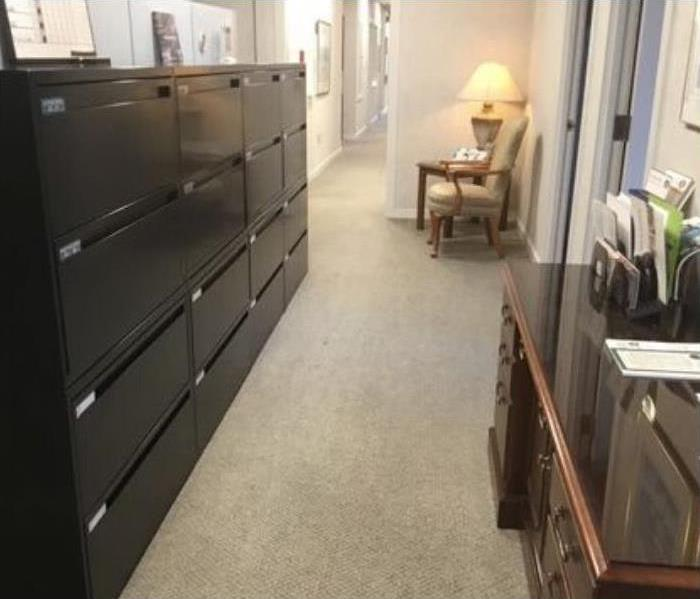 clean beige carpet with black filing cabinet with multiple drawers to the left and brown desk to the right and chair