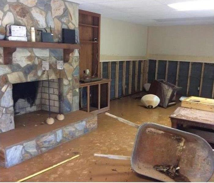 living room with stone fireplace, wheel barrel, book case, and other items on the brown floor.