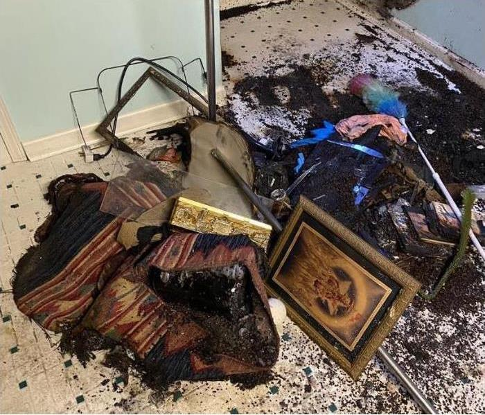 various home items including portraits and furniture charred on the floor in a laundry room.
