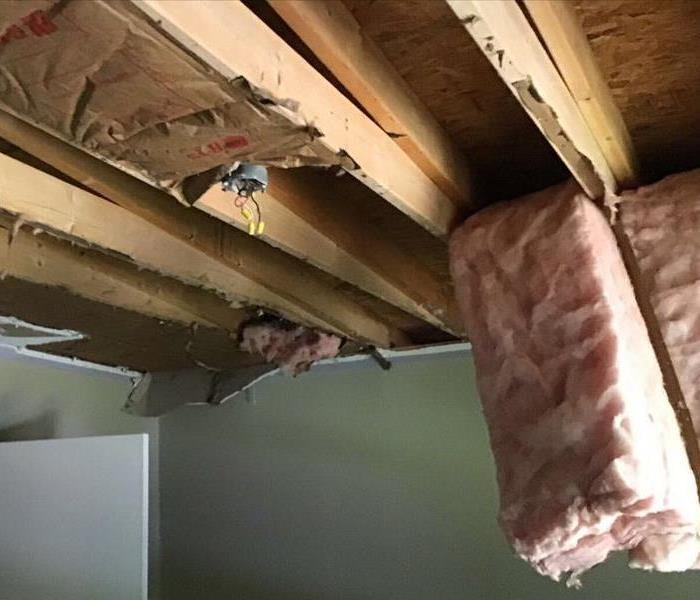 wooden ceiling with fiber insulation coming out
