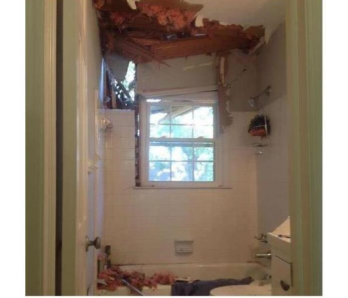 roof that has caved in on bathroom with window and tub. Insulation falling down into the bathroom.