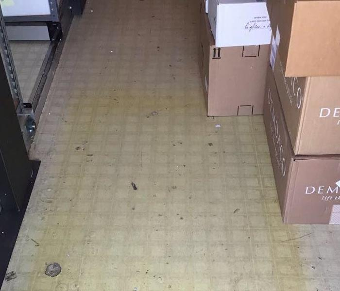 stock room tiled flooring with yellow stain from storm damage.  Shelving on the the left side and boxes on a stack of boxes.
