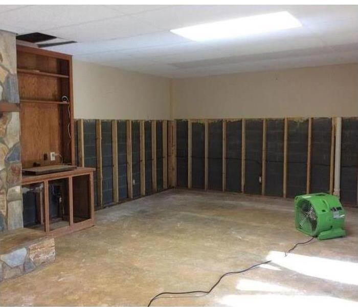 Living with fireplace and wall that has been partly taken out and a green SERVPRO vacuum machine.