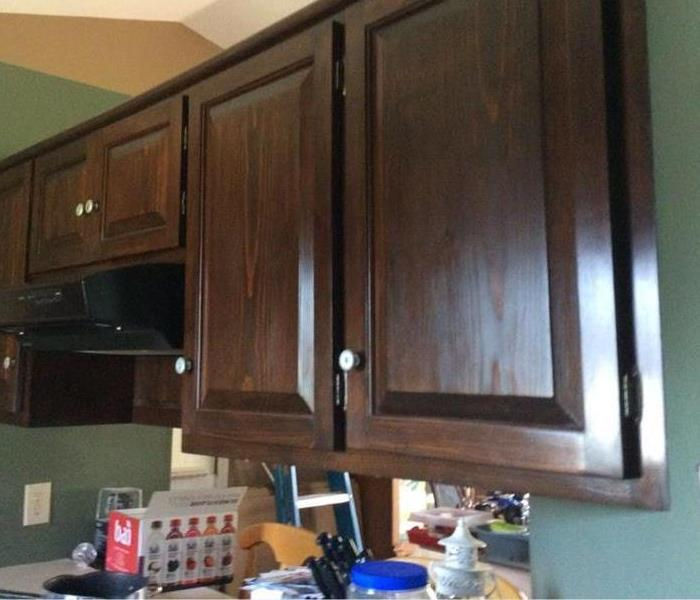 cherry cabinet kitchen, black stove, and beige countertops.