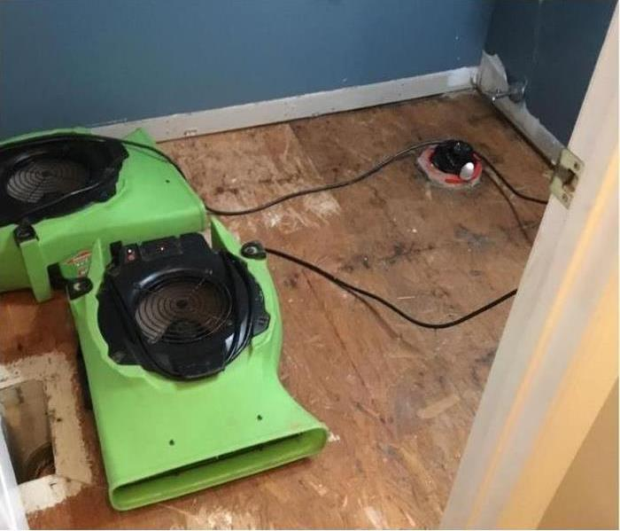 torn up flooring with two green air scrubbers and a light colored wall.