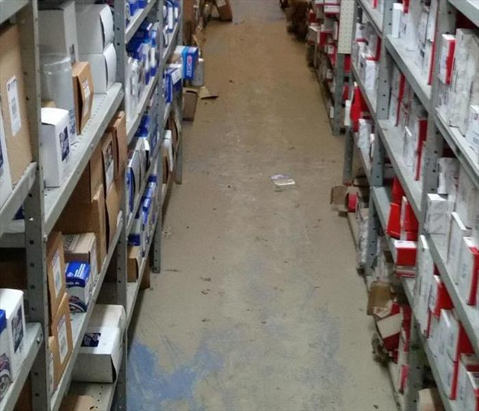 aisle of the store with shelving at the top with auto tools and tiled floor cleaned.
