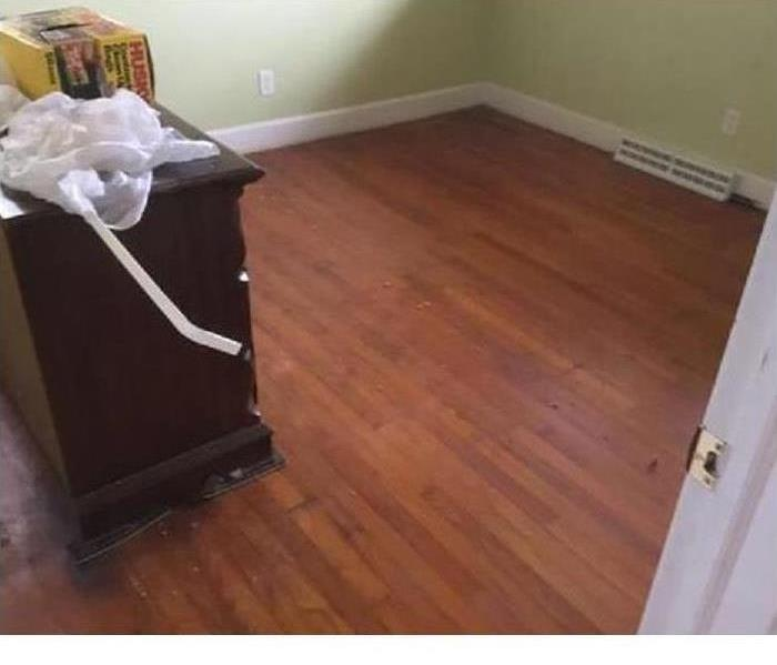 clean wood floor room with dresser with other items on top of it. Green wall all around the room.