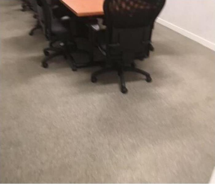 dirty beige carpet with long wooden brown desk that sits multiple black chairs around it.