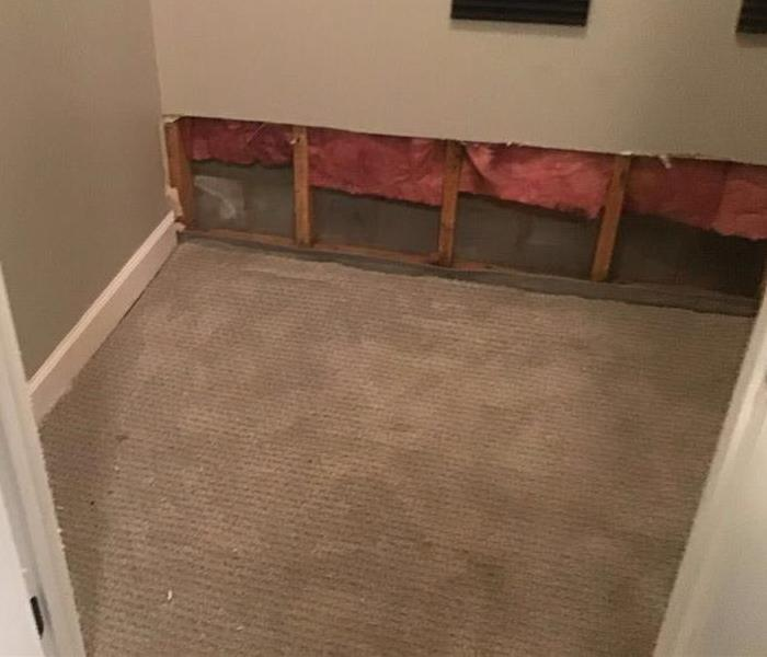 Beige flooring with parts of the wall near the floor torn out.